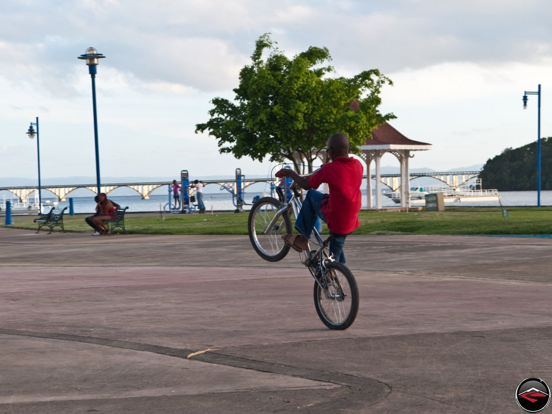local boy from the dominican republic rides a wheelie on his bicycle for tips
