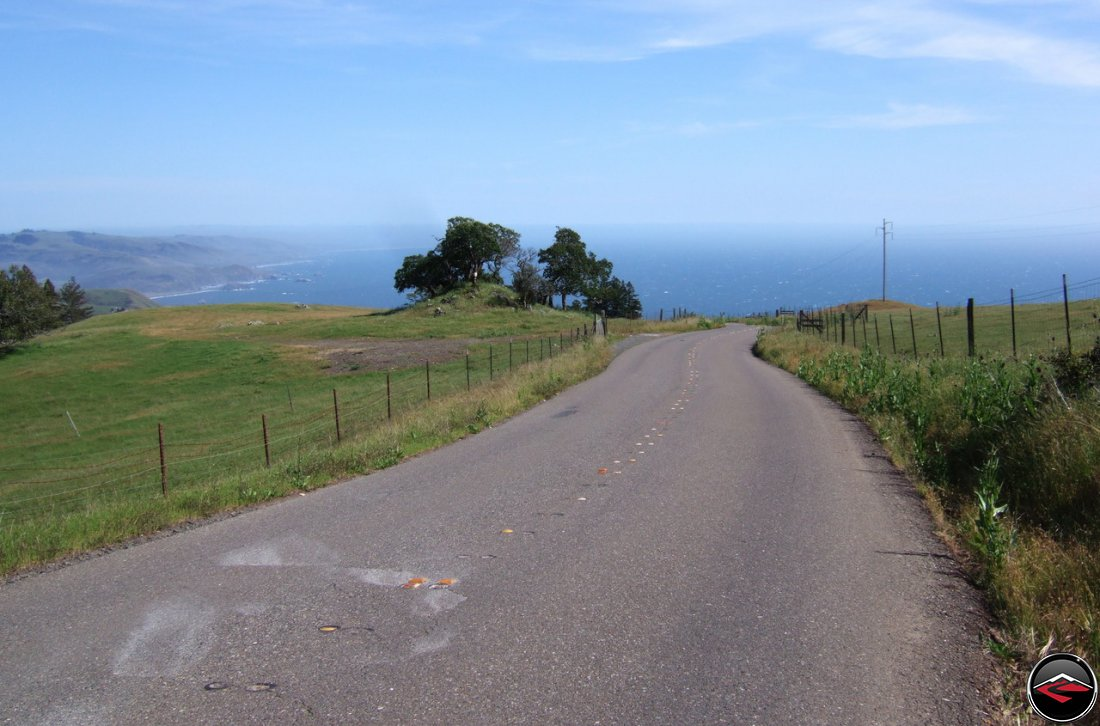 Narrow, windy, Pacific Coast Highway in Northern California with a calm Pacific Ocean in the distance