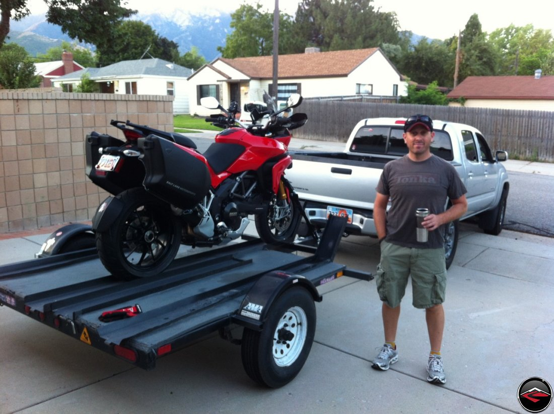 Dave drinking a cup of coffee, standing next to a Ducati Multistrada 1200 loaded on a 3-rail trailer attached to a Toyota Tacoma