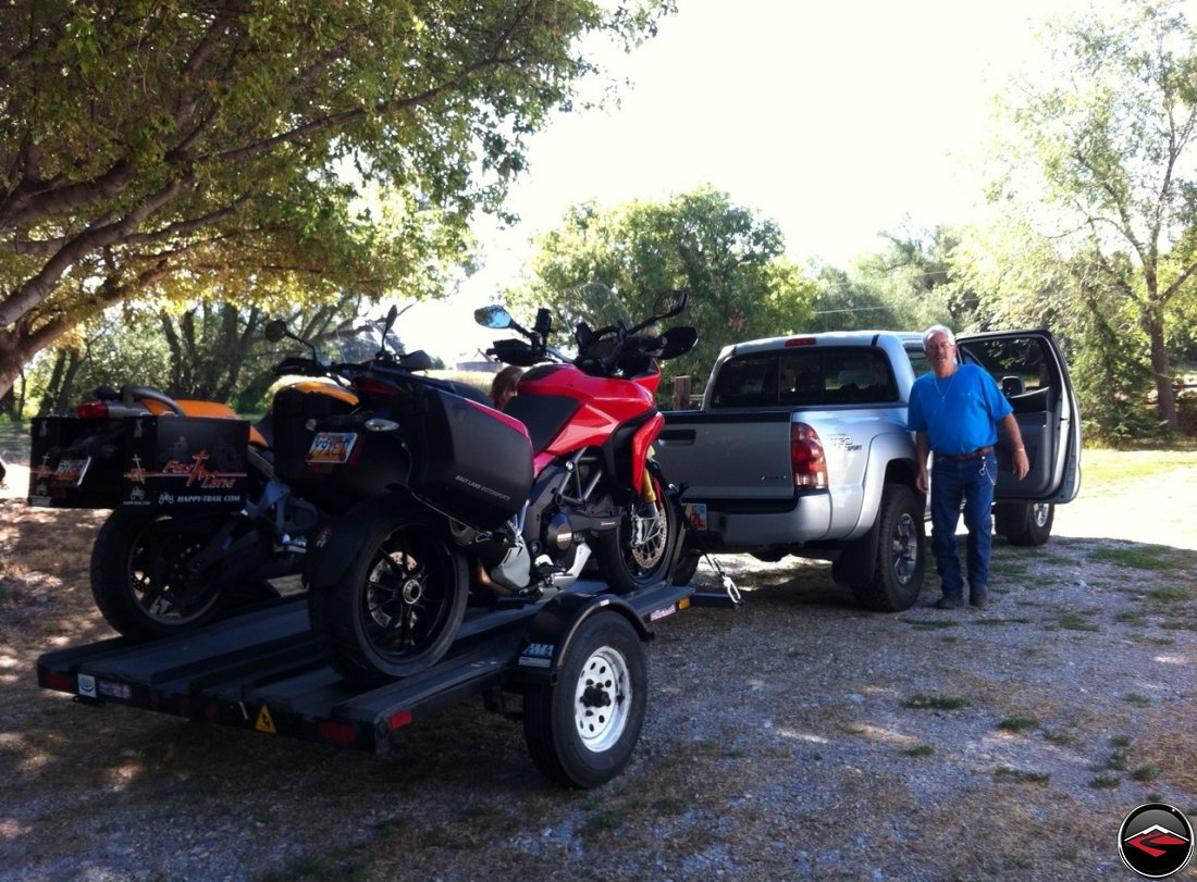 Tom standing next to a Toyota Tacoma with a Ducati Multistrada 1200 and a Buell Ulysses loaded on a 3-Rail Trailer