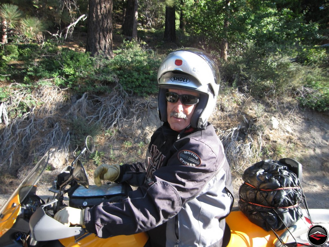 Dad, wearing a flip-face Shoei helmet while riding his Buell Ulysses, asking for directions