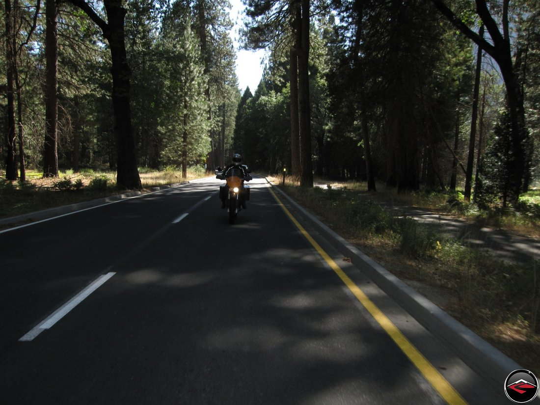 Tom riding his Buell Ulysses in the shade on the ashphalt in California's Yosemite National Park, Southside Drive
