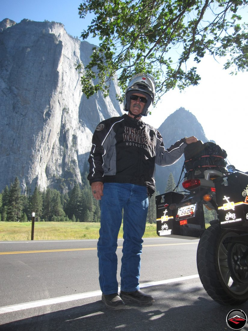 Tom standing next to his Buell Ulysses, fit with Pirelli Sync tires and Happy Trails saddlebags, with El Capitan in the background while visiting California's Yosemite National Park