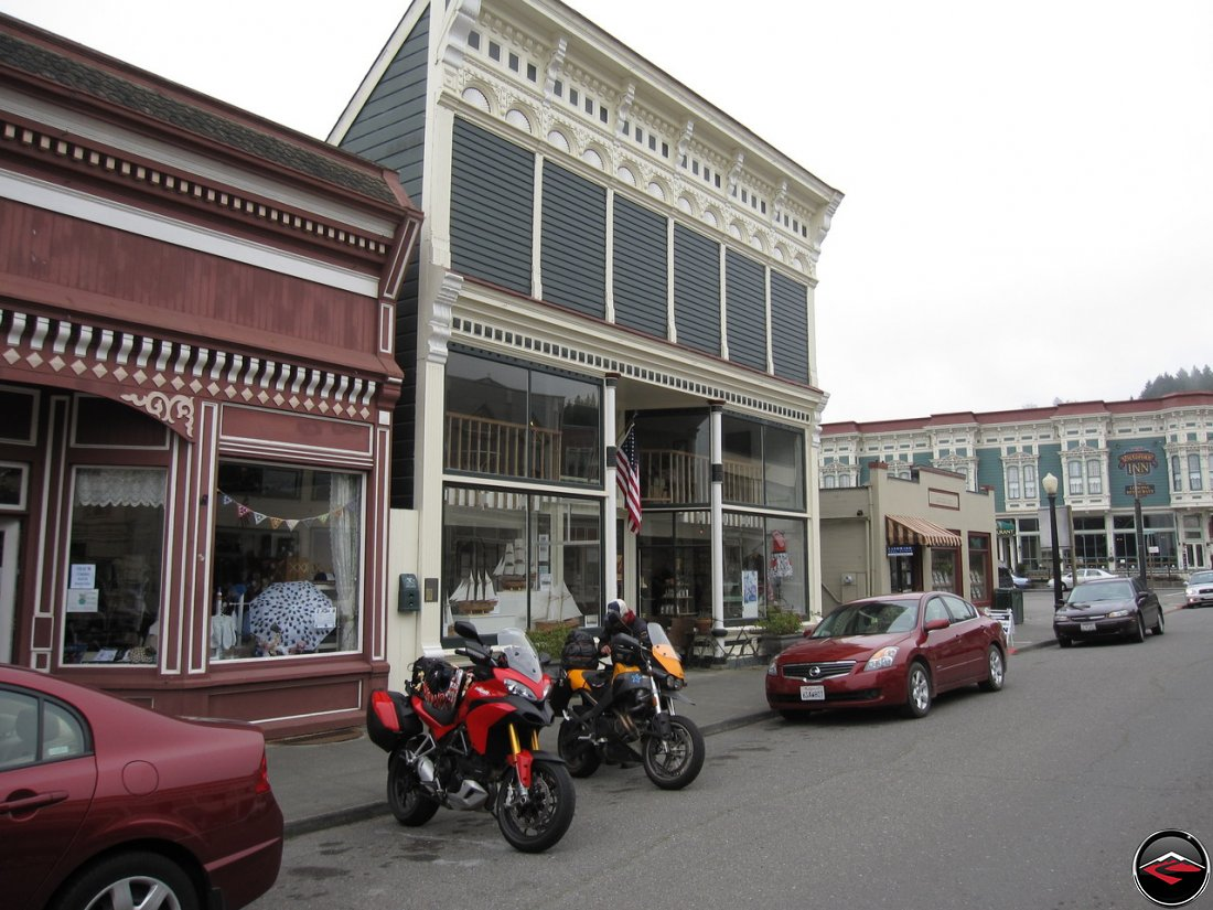 Two motorcycles, a Ducati Multistrada 1200 and a Buell Ulyssess parked on historic main street in Ferndale, California