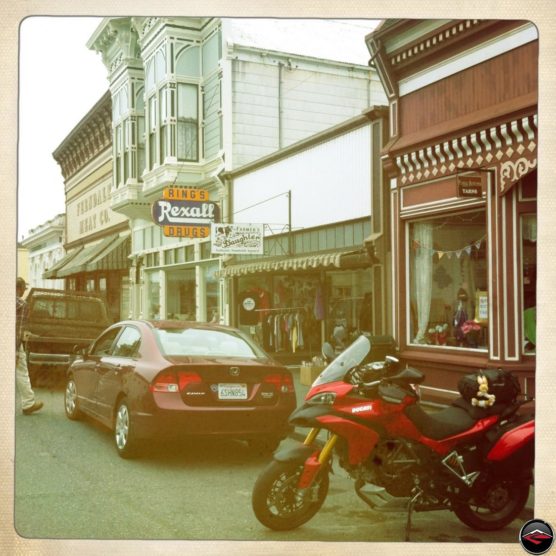 a Ducati Multistrada 1200 parked on historic main street in Ferndale, California, and a sign for Rings Rexall Drugs and Farmers Daughter