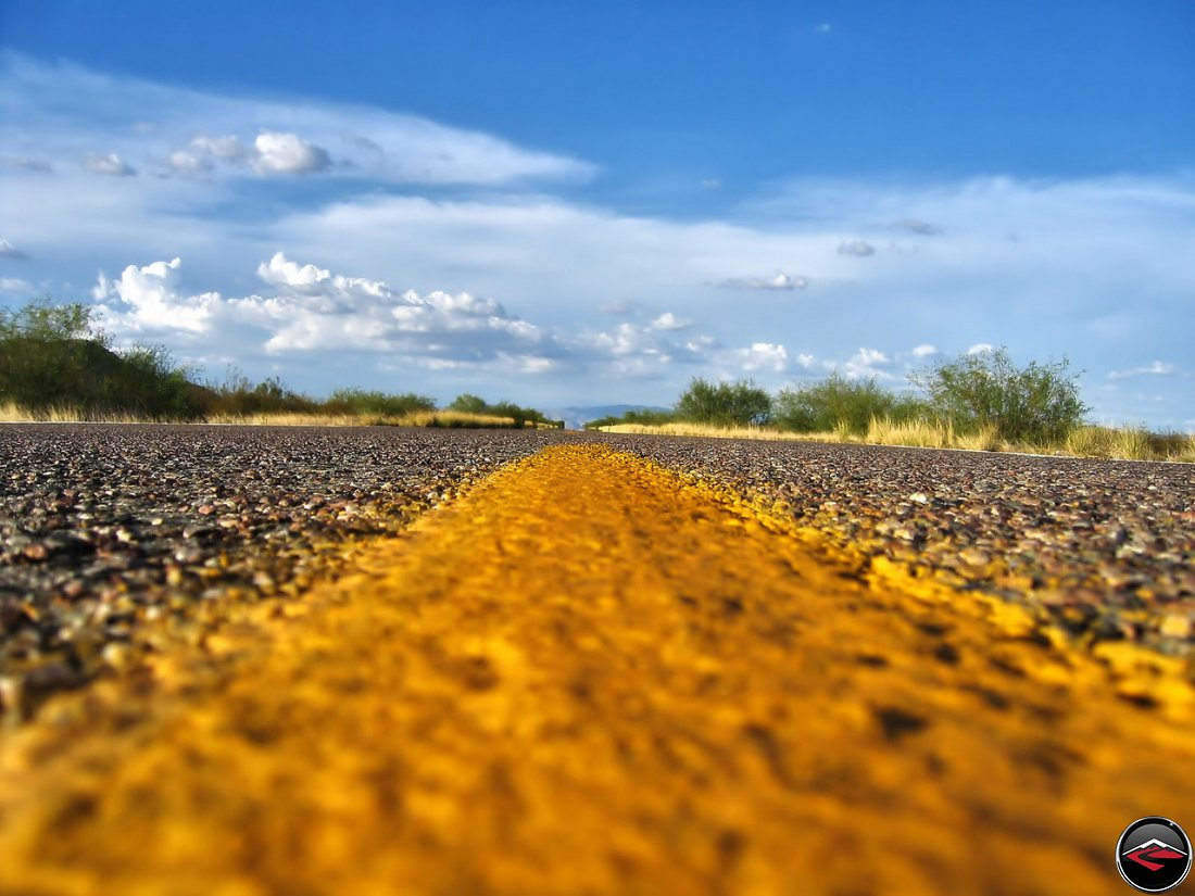 Yellow lines in the center of an Empty California Road, with scattered clouds in the distance