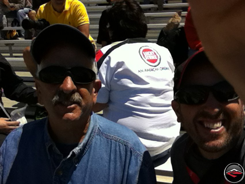 Tom and Dave sitting In the grandstands before the 2012 MotoGP race