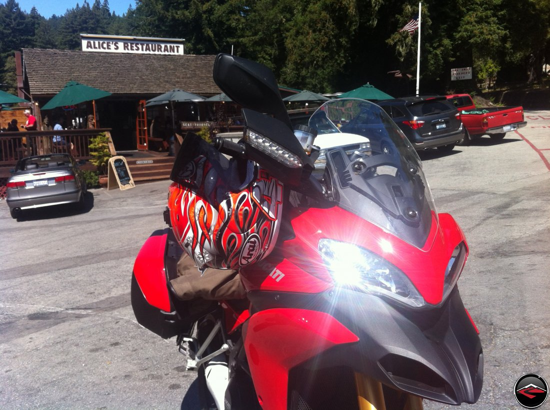 Ducati Multistrada 1200, with headlight gleam and glint, parked in front of Alices Restaurant along California Highway 35, Skyline Blvd, and Highway 84, La Honda Road. Haga replica Arai Helmet