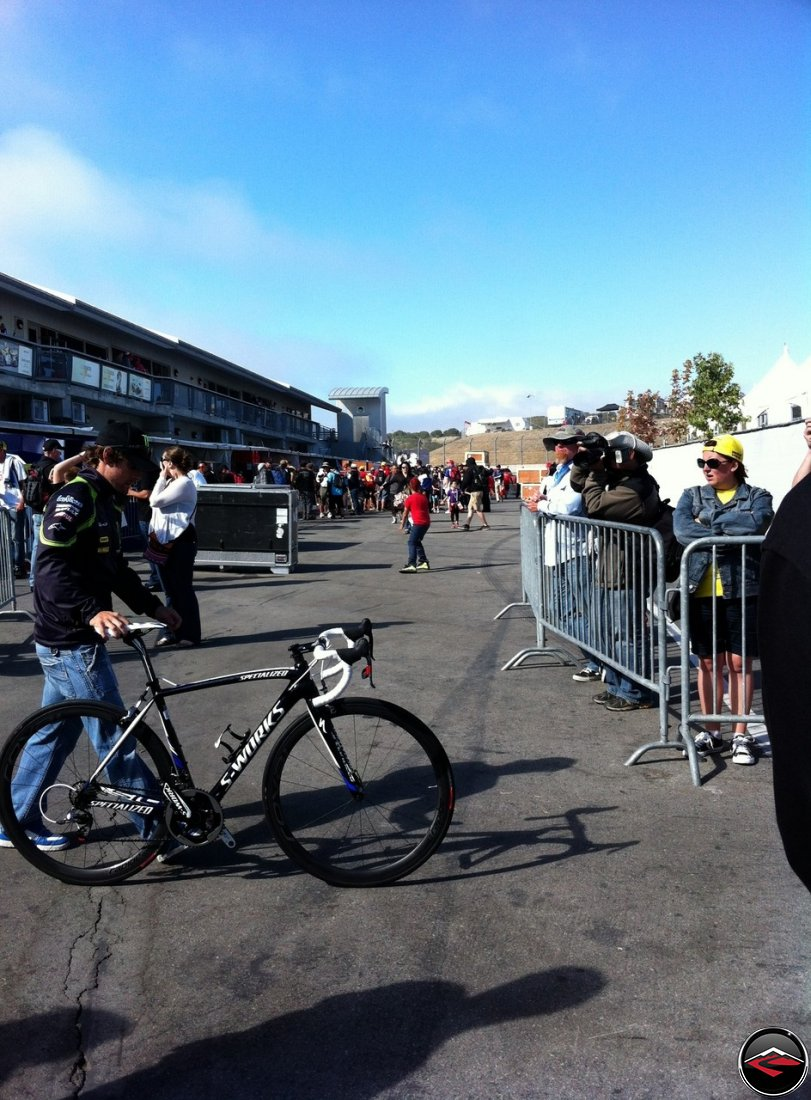 Cal Crutchlow, MotoGP Tech3 Rider, pushes his Specialized S-Works bicycle across the paddock