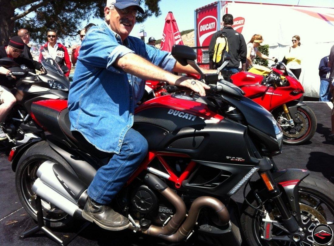 Tom sitting on a Ducati Diavel Black Carbon at Mazda Laguna Seca Raceway, during the 2012 MotoGP races