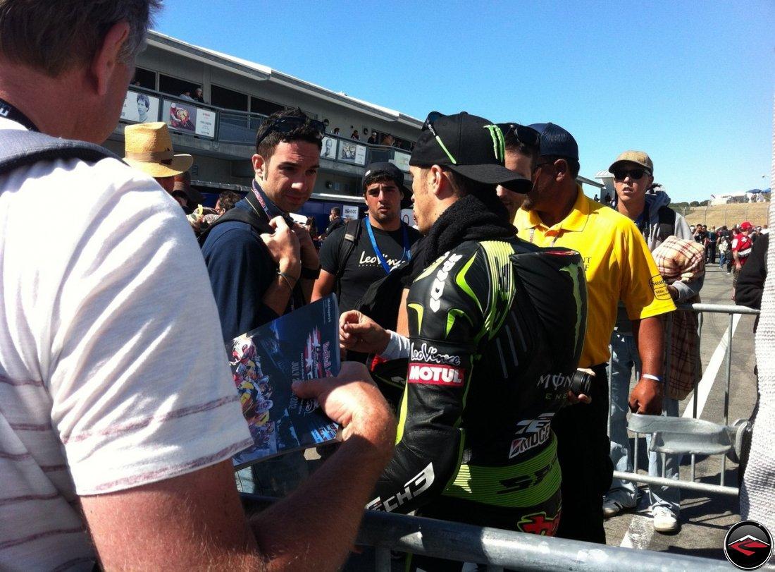 2012 MotoGP Tech 3 Racer Andrea Dovizioso, wearing Green Spidi Leathers, signing autographs at Laguna Seca raceway