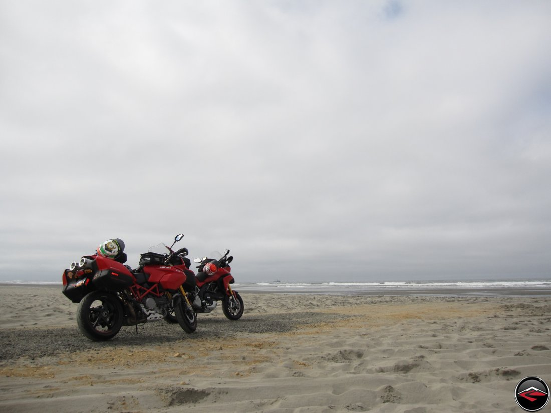 Two Red Ducati Mulstistrada S motorcycles parked ont he beach looking over the Pacific Ocean